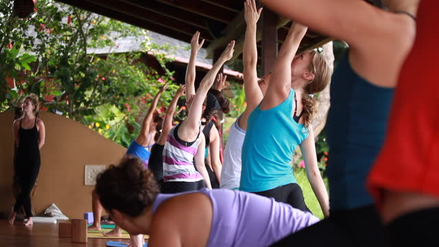 medium close up of a group of women practising yoga on an outdoor yoga deck surrounded by lush vegetation - kelly mason videos stock videos & royalty-free footage