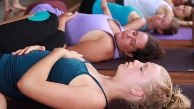 medium close up of a woman lying down on her yoga mat putting her hand on her heart and the other hand on her stomach with other women in the background on yoga mats in yoga attire - kelly mason videos stock videos & royalty-free footage