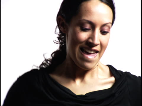 medium close up of a young woman as she dances against a white background - baggy jeans stock videos & royalty-free footage