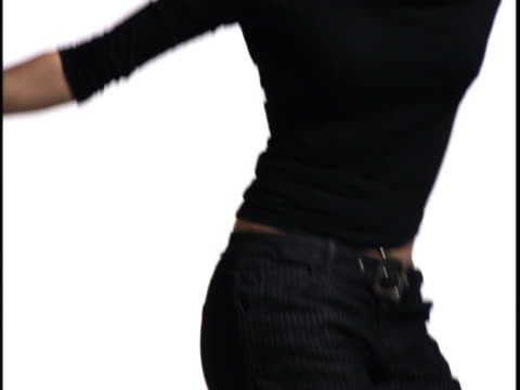 medium close up of a young woman as she playfully dances against a white background - baggy jeans stock videos & royalty-free footage