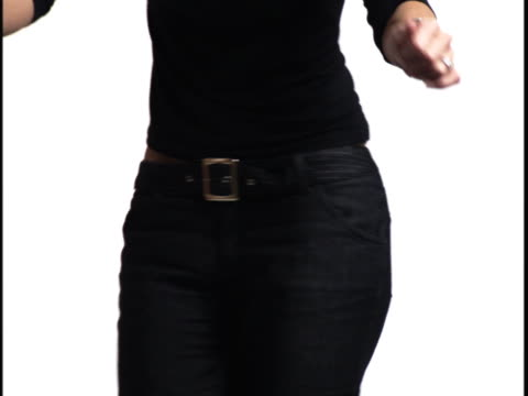 medium close up of a young woman as she shakes and dances against a white background - baggy jeans stock videos & royalty-free footage