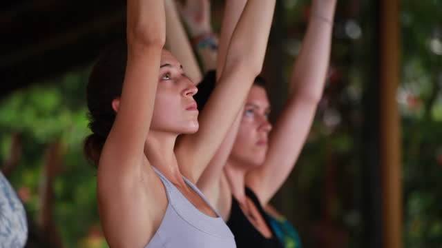 medium close up of hands, changing yoga postures ,using yoga blocks, with a group of women practising yoga and colourful yoga mats - kelly mason videos stock videos & royalty-free footage