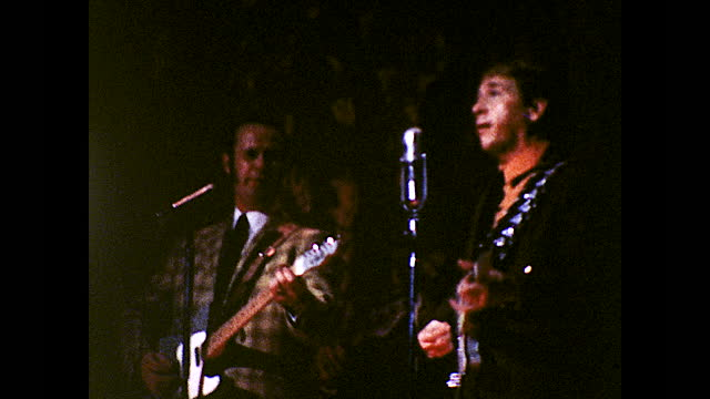 medium close up of two men both with guitars singing on stage, they take turns solo - 1960 1969 stock videos & royalty-free footage