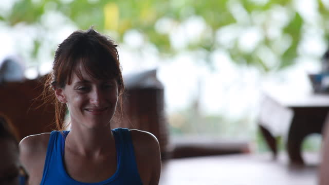medium close up of woman sleeveless t-shirt watching and smiling and then briefly looking into the camera - kelly mason videos stock videos & royalty-free footage