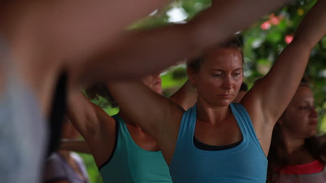 medium close up of women reaching up to the sky practising yoga in colourful yoga attire - kelly mason videos stock videos & royalty-free footage