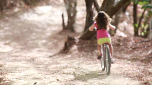 medium close up of young girl riding away from camera down a long windy country road, standing up along the way. - kelly mason videos stock videos & royalty-free footage
