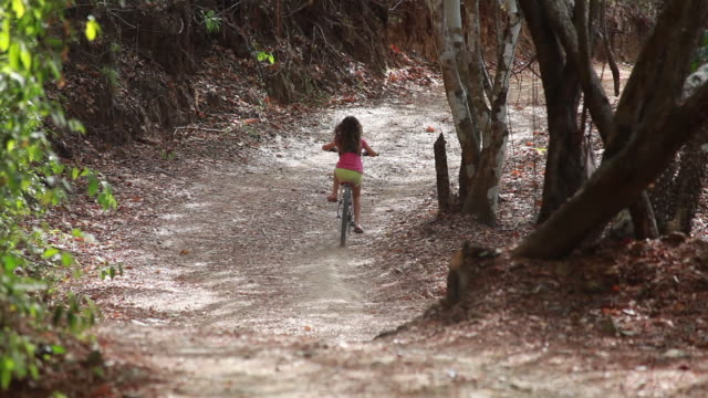 medium close up of young girl riding away from camera down a long windy country road - kelly mason videos stock videos & royalty-free footage