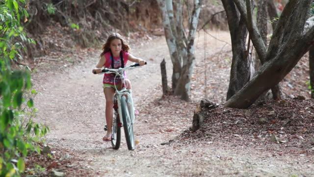 vidéos et rushes de medium close up of young girl riding bike toward camera down a long country road - kelly mason videos