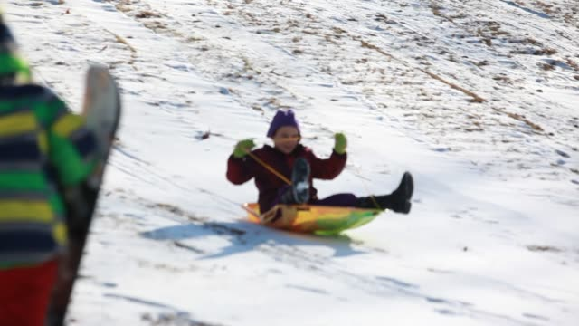 medium close up of young girl tobogganing down snowy hill on toboggan - kelly mason videos stock videos & royalty-free footage