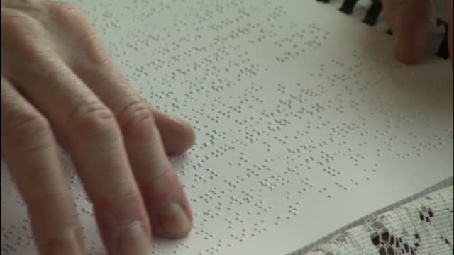 vidéos et rushes de medium close up pan-left - a blind person reads braille on a page. - aveugle