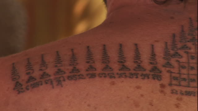 Medium Close Up pan-right - A man bears tattoos which depict magic spells across his shoulders. / Thailand
