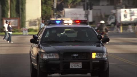 medium close up pan-right - a police car drives on a city street/hollywood, california, usa - surveillance stock videos & royalty-free footage