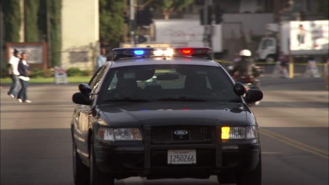 medium close up pan-right - a police car drives on a city street/hollywood, california, usa - police car stock videos & royalty-free footage