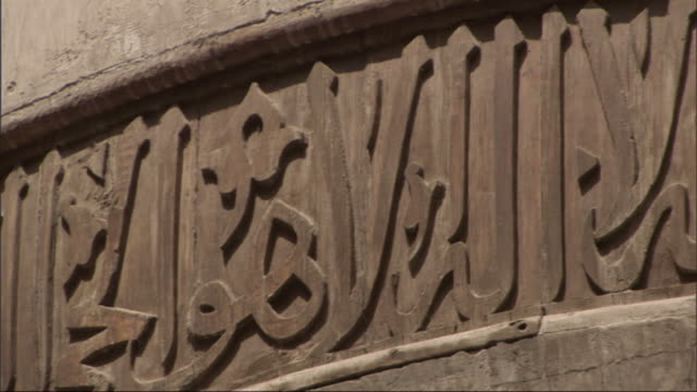 medium close up, pan-right - carved letters decorate an archway / egypt - arabic script stock-videos und b-roll-filmmaterial