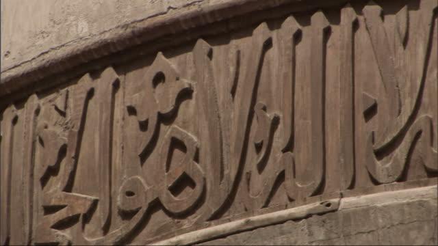 vidéos et rushes de medium close up, pan-right - carved letters decorate an archway / egypt - moyen oriental
