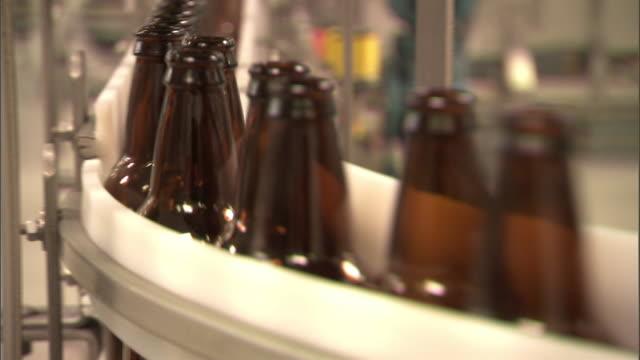 Medium Close Up pan-right rack-focus tilt-down tilt-up-Beer bottles move through a factory on a conveyor belt. / Missouri, USA