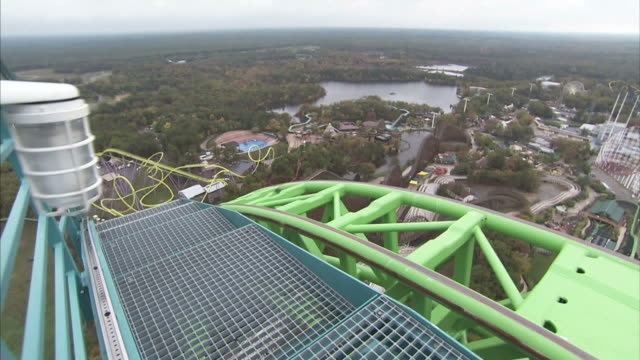 medium close up pan-right - the kingda ka roller coaster races past a maintenance platform / six flags great adventure jackson, nj - jackson new jersey stock videos and b-roll footage
