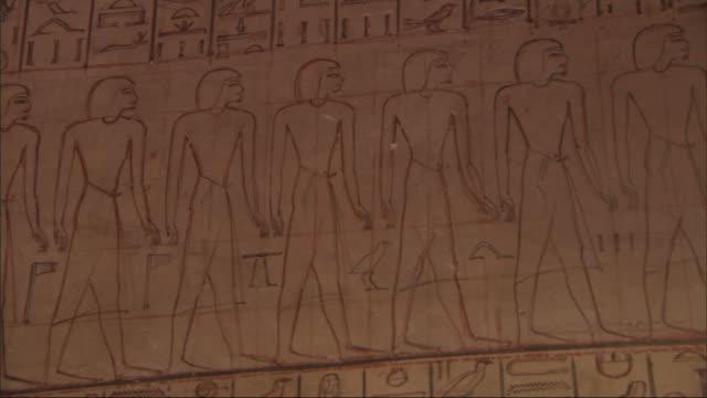 medium close up, pan-right tilt-down - a mural depicts egyptian figures and hieroglyphics / egypt - 壁画点の映像素材/bロール