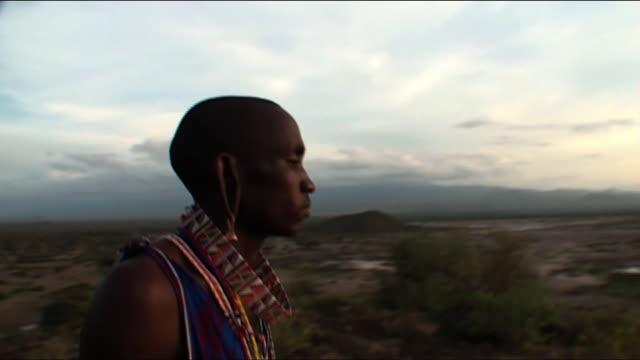 Medium Close Up pan-right tracking-left - A Masai man looks toward a sunset. / Kenya