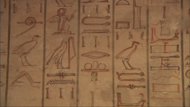 Medium Close Up, pan-right  tracking-right - A mural depicts hieroglyphics / Egypt