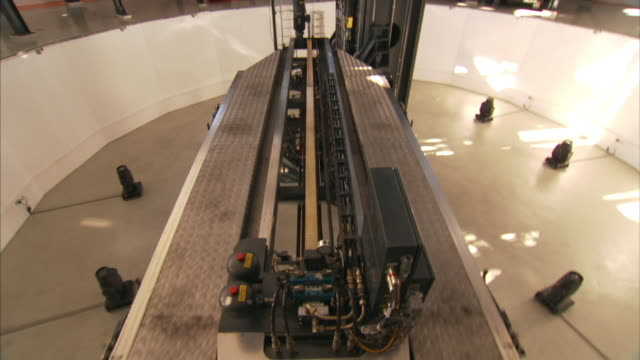 medium close up push-in tilt-up - a complex piece of hydraulic equipment retracts. / wolfsburg, germany - wolfsburg lower saxony stock videos and b-roll footage