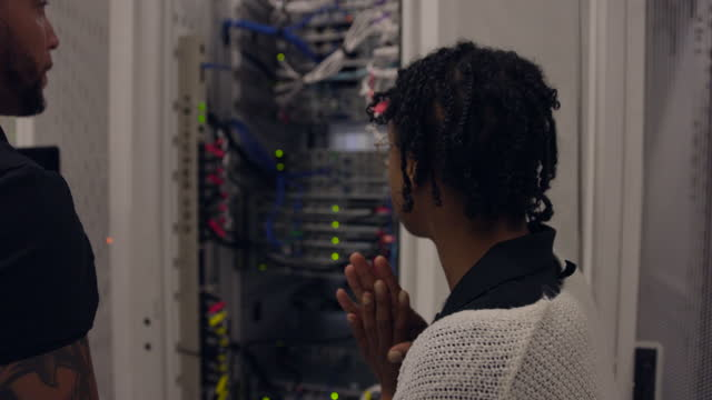 medium close up shot of it professionals in discussion while working on server rack in data center - scrutiny stock videos & royalty-free footage