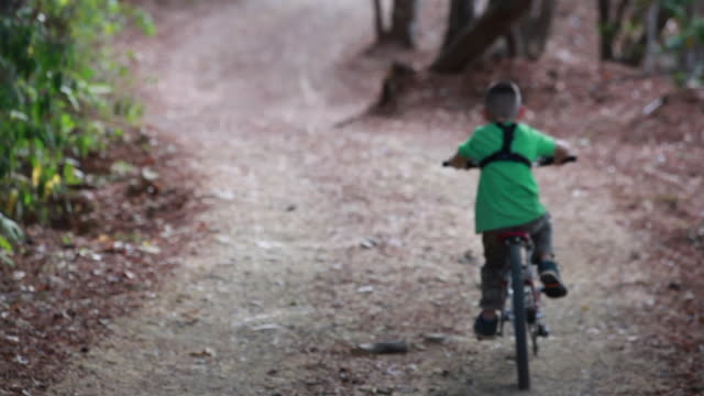vidéos et rushes de medium close up shot of young boy riding away on a bicycle along a rural road surrounded by nature. - kelly mason videos