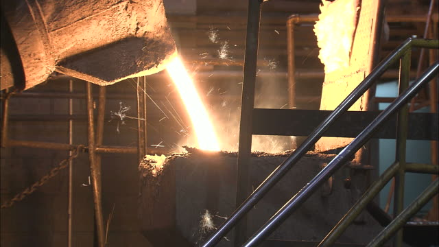 Medium Close Up static - A cast iron bucket pours molten metal into a container /  Ohio, United States