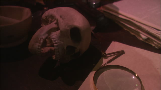 Medium Close Up static - A hand holds a magnifying glass over a human skull/Exeter, England
