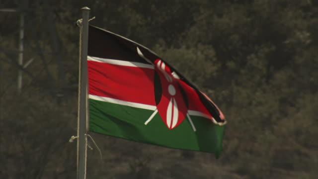 medium close up static - a kenyan flag blows in the wind. / olkaria, kenya - kenyan flag stock videos & royalty-free footage