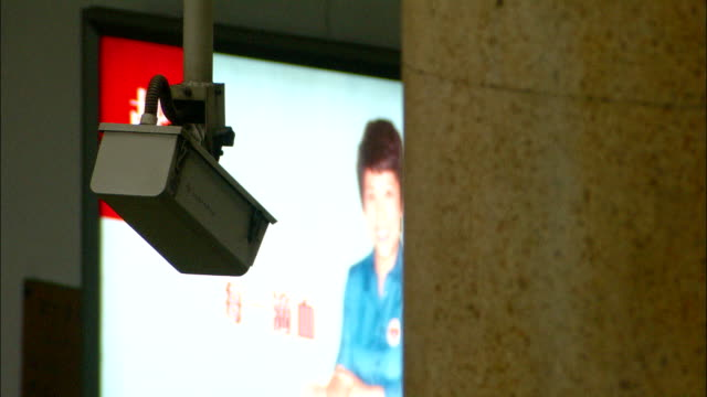 Medium Close Up static - A surveillance camera operates on a platform of the Beijing Subway./Beijing, China
