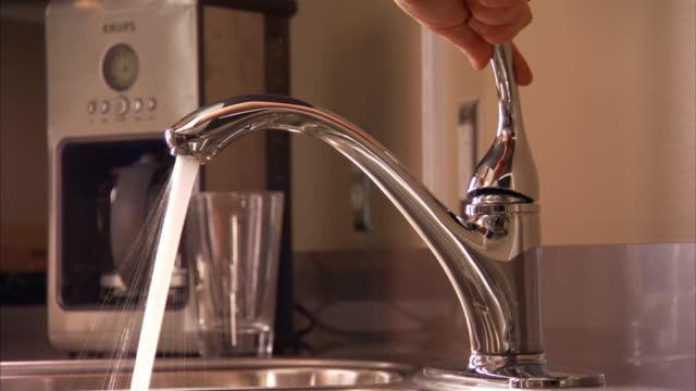 medium close up static - a woman turns the water on and off at her kitchen sink.   - zapfen stock-videos und b-roll-filmmaterial