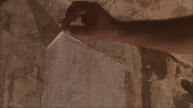 medium close up, static - an archeologist gently peels paper toweling away from a stone wall to reveal egyptian hieroglyphs - archaeologist stock videos & royalty-free footage