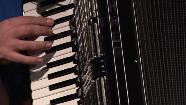 vídeos y material grabado en eventos de stock de medium close up static - an assembler tests the treble keyboard of an accordion /  germany - acordeonista