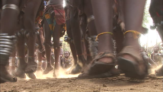 Medium Close Up static - Ethiopian women jump up and down with bells and bracelets on their ankles. / Ethiopia
