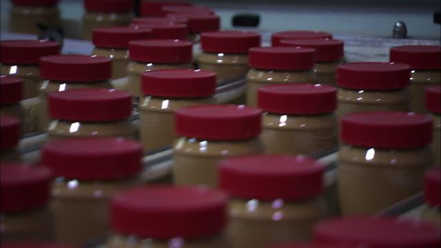 medium close up static - jars of peanut butter move along a conveyor. / georgia, usa - peanut food stock videos and b-roll footage