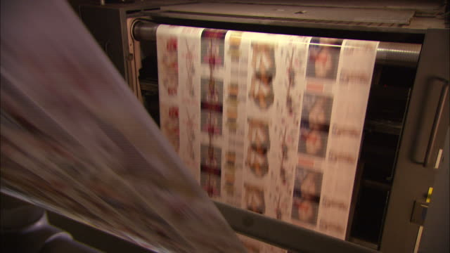 medium close up static - long sheets of printed paper run through a printing press /  wisconsin, united states - magazine publication stock videos & royalty-free footage
