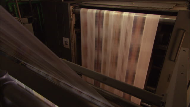 medium close up static - long sheets of printed paper speed through rollers in a printing press /  wisconsin, united states - magazine stock videos & royalty-free footage