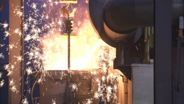 medium close up static - sparks fly as molten metal pours into a vat /  ohio, united states - metal stock videos & royalty-free footage
