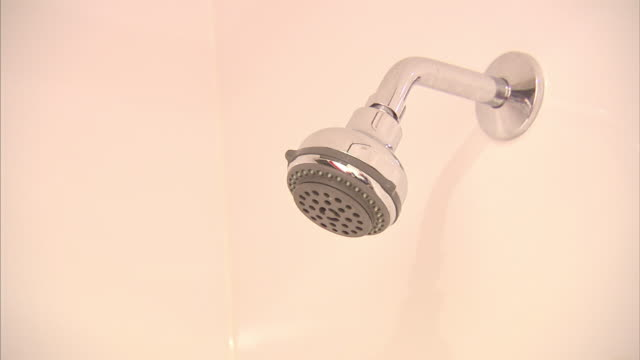 medium close up static - water sprays spontaneously from a shower head.   - shower head stock videos & royalty-free footage