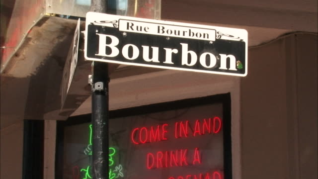 vídeos de stock, filmes e b-roll de medium close up - street sign reads rue bourbon near storefront with neon signage / new orleans louisiana - placa de nome de rua