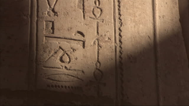 Medium Close Up, tilt-up - Ancient Egyptian hieroglyphics cover a stone wall