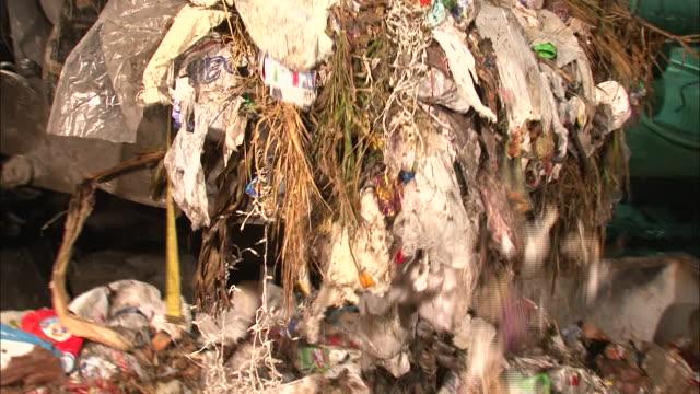 vídeos de stock, filmes e b-roll de medium close up zoom out - trash being dumped into garbage receptacle  / new orleans louisiana - saco de lixo