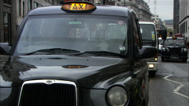 medium close up zoom-out - a black cab slowly moves in london traffic. / london, england, uk - taxi stock videos & royalty-free footage