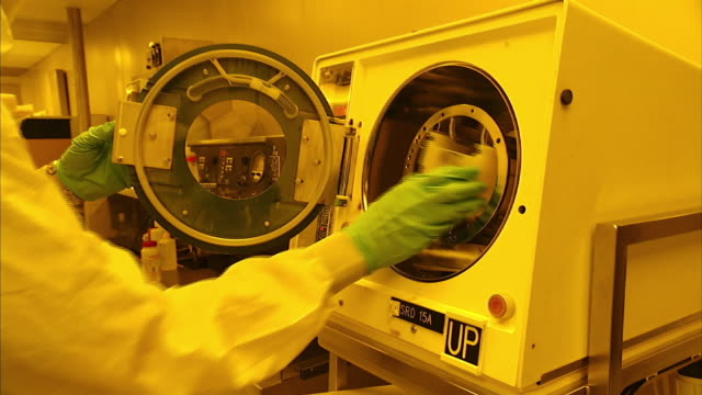 medium close up_hand-held push-in - a lab technician wears sterile clothing and gloves when a sample is inserted into a centrifuge.   - 遠心機点の映像素材/bロール