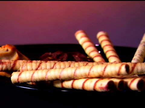 vídeos de stock, filmes e b-roll de medium close-up of a rotating plate of various cookies. - equipamento doméstico
