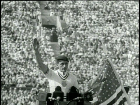 medium closeup of american olympic team member lt george c calnan stands at a podium with american flag and microphones raising his arm and speaking... - 1932 stock videos & royalty-free footage