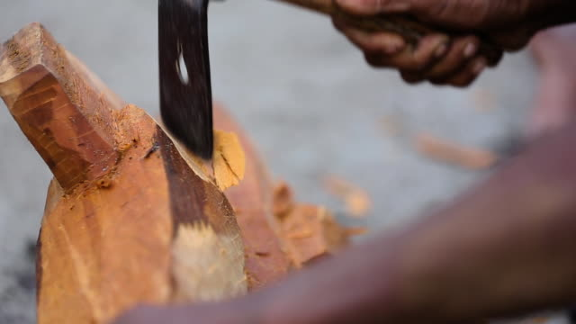 medium closeup of man using adze, or axe-like tool, to carve wood - pacific islands stock videos & royalty-free footage
