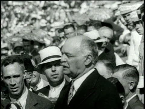 medium closeup of united states vice president charles curtis speaking with audience immediately behind him / wide pan of athletes and stadium... - 1932 stock-videos und b-roll-filmmaterial