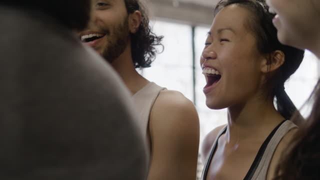 vídeos de stock, filmes e b-roll de medium close-up shot of dance troupe and female choreographer with tablet laughing - instrutor de fitness